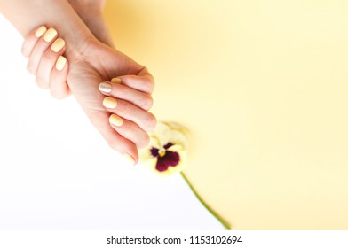 Stylish trendy female manicure. Beautiful young woman's hands on yellow and white background. Summer concept.