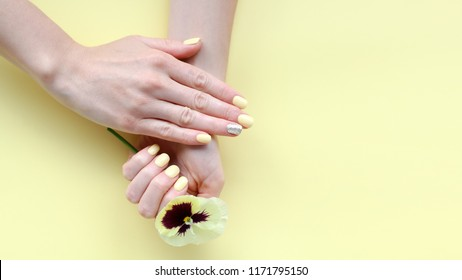 Stylish trendy female manicure. Beautiful young woman's hands with flower on yellow background.