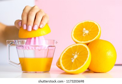 Stylish trendy female manicure. Beautiful young woman's hands on pink background takes juicy oranges on pink background . Manicure concept, juice concept.