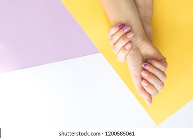 Stylish trendy female manicure. Beautiful young woman's hands on abstract geometric paper background.. Manicure concept.