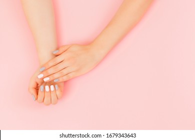 Stylish trendy female manicure. Beautiful young woman's hand with perfect pink and grey manicure on pink background. Flat lay style.