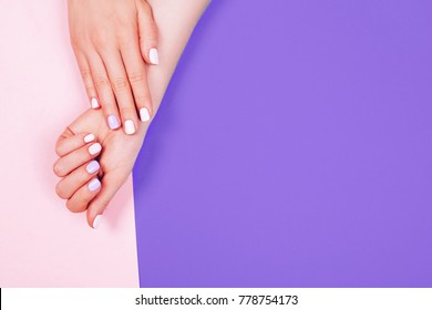 Stylish trendy female manicure. Beautiful young woman's hands on pink and Ultra Violet background. Concept of demonstrating color of the year 2018. Macro. Frame with code and name of color.