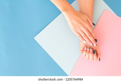 Stylish trendy female pink and blue manicure. Beautiful young woman's hands on geometric pattern background. Trendy geometric pattern.