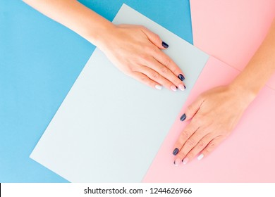 Stylish trendy female pink and blue manicure. Beautiful young woman's hands on pink pastel background with festive multicolored confetti. Trendy geometric pattern.