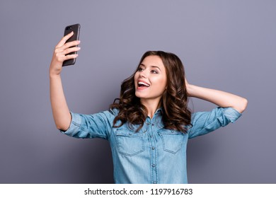 Stylish trendy funny flirty nice cute cheerful adorable lovely attractive magnificent brunette girl with wavy hair in casual denim shirt, taking cool selfie on cam, isolated over grey background