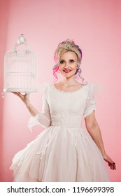 Stylish and trendy girl in a white dress. Creative hair coloring. Multi-colored hairstyle. Concept with an empty bird cage. Pink background