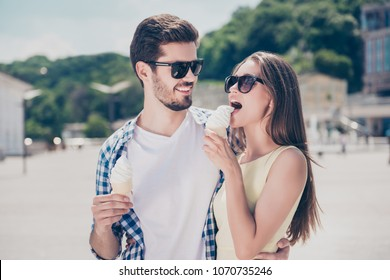 Stylish trendy man and woman holding sweet tasty delicious ice cream in the waffle cone, enjoying cold dessert in hot sunny weather
