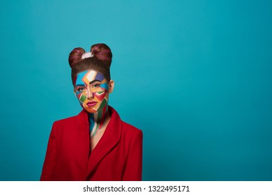 Stylish, trendy model wearing in red jacket, posing in studio with blue background. Cool girl has creative pop art make up on face and nice bow hairstyle. Funky lady looking at camera, posing.