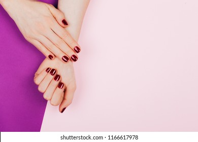 Stylish trendy red female manicure. Beautiful young woman's hands on pink and Ultra Violet background.
