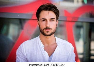 Stylish trendy young man standing outdoor against office window, looking confindent at camera