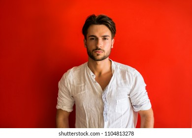Stylish trendy young man standing outdoor against red wall, looking confindent at camera
