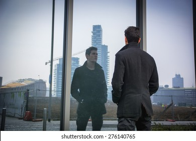 Stylish trendy young man standing outdoor in front of office window, looking at his reflection