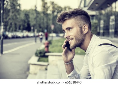 Stylish trendy young man talking on cell phone, outdoor next to office window, looking confident away