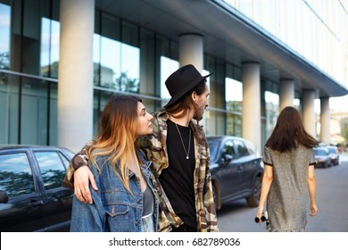 Stylish unfaithful young male hugging his fashionable girlfriend and gazing after another girl who just walked by them. People, relationships, romance, love triangle, jealousy and infidelity concept