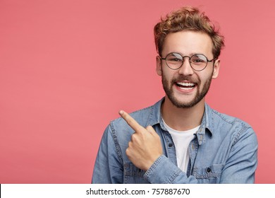 Stylish unshaven man in denim shirt points at copy space on pink wall as shows something pleasant, has smiling look, advertises product. Look over here! People, advertising, emotions concept