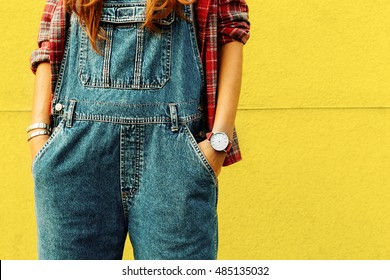 Stylish Urban Girl in shirt and Denim overalls in the City