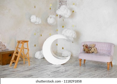 Stylish vintage children room. Kid's room with pink soft sofa and toy bears on it, wooden moon and textile clouds