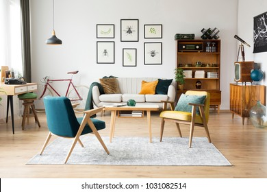 Stylish vintage furniture in a spacious flat interior with beige sofa, chairs and posters on the wall