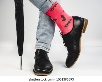 Stylish, vintage shoes, bright, funny socks with a pattern, black umbrella and men's legs on a white background. Style, fashion, beauty, mood