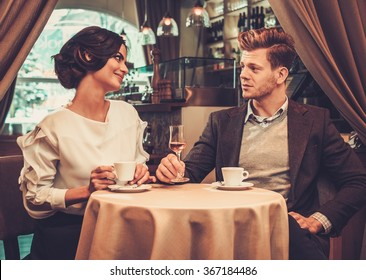 Stylish wealthy couple drinking coffee in restaurant.