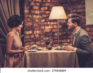 Stylish wealthy couple enjoying meal at restaurant.