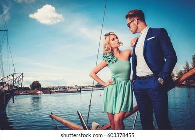 Stylish wealthy couple on a luxury yacht.