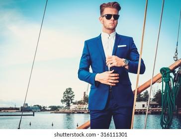 Stylish wealthy man on a luxury wooden regatta