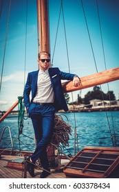 Stylish wealthy man on a luxury wooden regatta.