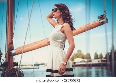 Stylish wealthy woman on a luxury wooden regatta