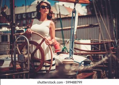 Stylish wealthy woman on a luxury wooden regatta.