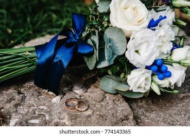 Stylish wedding bouquet flowers from bush roses, eustoma and gold wedding rings on the stone on the background nature. Wedding ceremony. Close up.