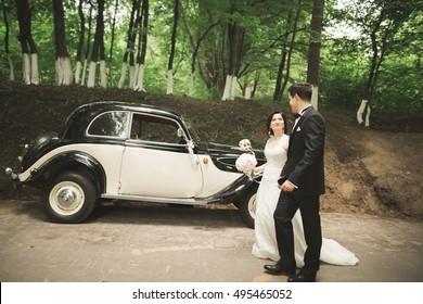 Stylish wedding couple, bride, groom kissing and hugging near retro car in autumn