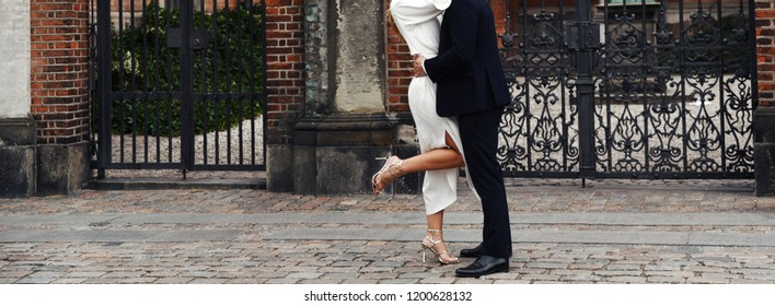 stylish wedding couple embracing at street, groom and bride just happy together
