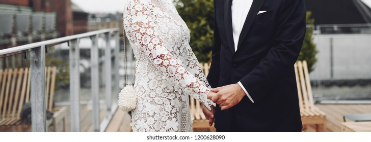 stylish wedding couple holding hands, groom and bride just happy together