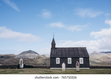 A stylish wedding couple stands out of Black wooden church of Budir in Iceland. Look to each other Blue sky with clouds mountains on the backgrond. perfect wedding day Film photo  Soft focus