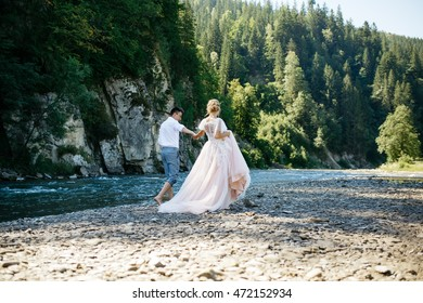 Stylish wedding couple walks on the stones by the mountain river