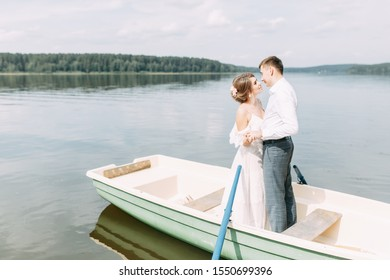 Stylish wedding in European style. Happy couple on a boat on the lake.