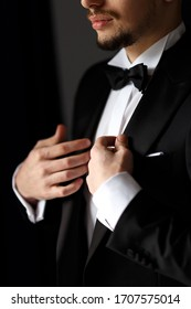 stylish wedding morning cooking groom in a suit.a man dresses in a white shirt and black suit