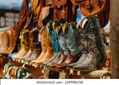 Stylish western boots with colorful embroidery on a shelf