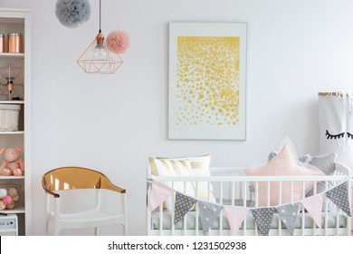 Stylish white and brown chair next to crib with pillows in trendy baby room with golden poster on the wall