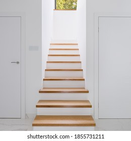 Stylish white corridor with wooden stairs, white doors and window on second floor
