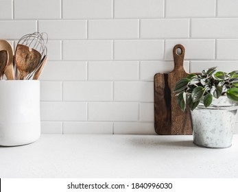 Stylish white kitchen background with kitchen utensils and green houseplant standing on white countertop, copy space for text, front view