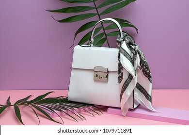 Stylish white leather female bag with a silk scarf on the small pink boards on the peach surface on the violet background in the studio. There are green branches next to it. Closeup. Horizontal.