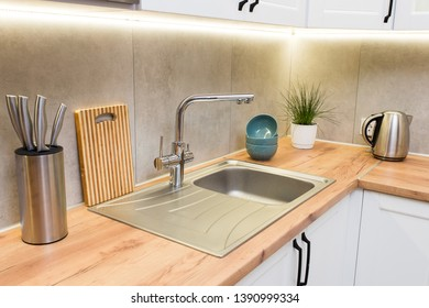 Stylish white scandinavian kitchen interior with decor accessories on wooden tabletop. modern home design.