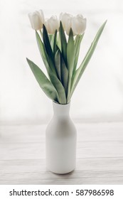 stylish white tulips in minimalistic fashionable vase on wooden rustic windowsill in soft morning light. hello spring concept, space for text