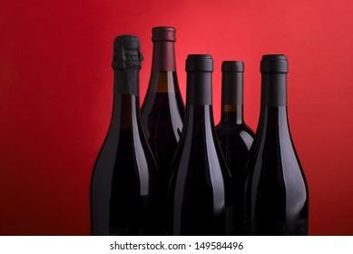 Stylish wine bottles on red background
