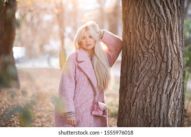 Stylish woman 20-24 year old with long hair wearing pink winter coat leaning on tree in park close up. Lokking at camera. 20s.