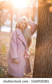 Stylish woman 20-24 year old wearing trendy winter coat posing over nature background in park. Looking at camera. Autumn season.