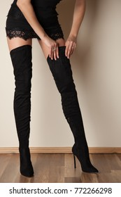 Stylish woman in black dress with lace details wearing overknee boots
