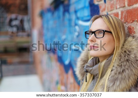 stylish woman with black glasses leaning against a brick wall and looking up in thoughts